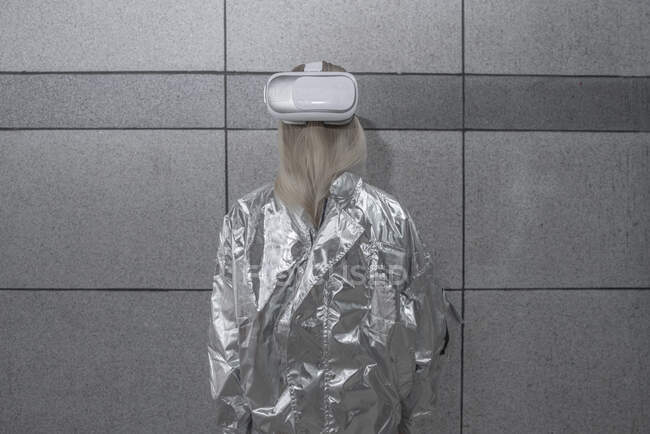 Rear view of girl in silver suit wearing VR goggles on back of head — Stock Photo