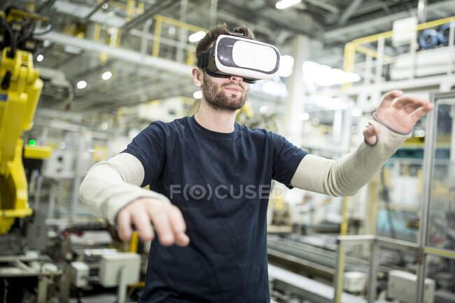 Hombre con gafas VR en fábrica moderna - foto de stock