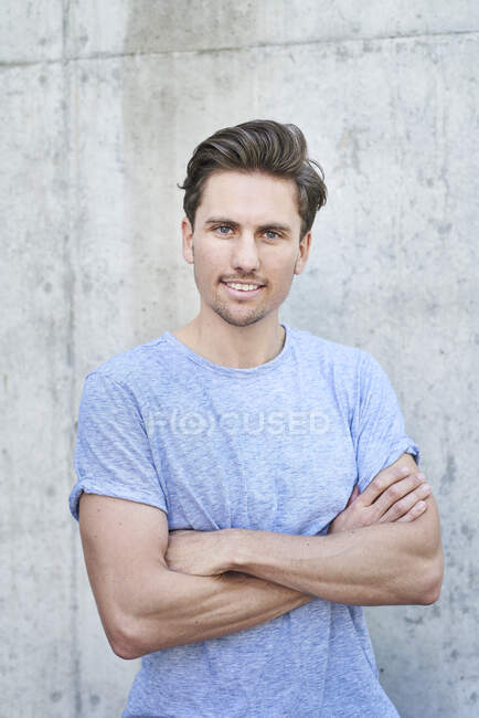 Portrait of man with arms crossed wearing grey t-shirt in front of concrete wall — Stock Photo