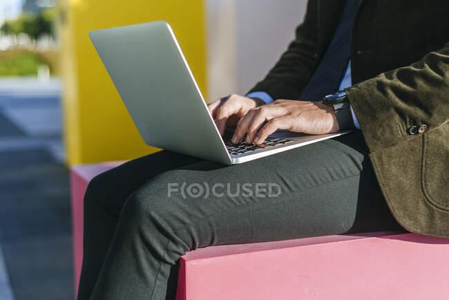 Витягнення рук бізнесмена за допомогою ноутбука на вулиці — стокове фото