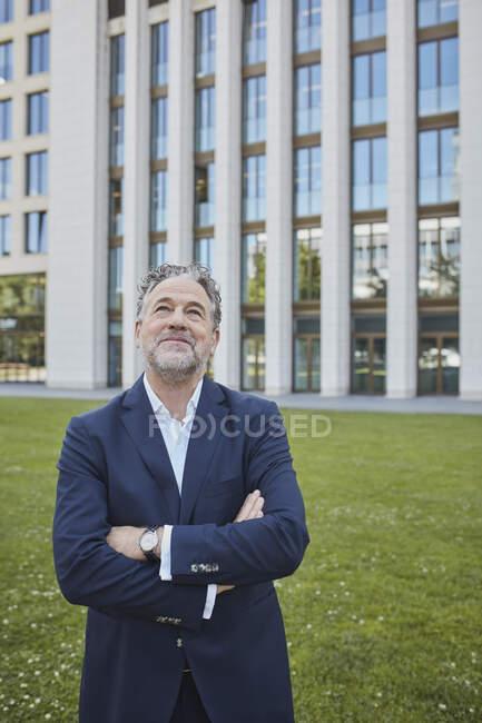 Зрілий бізнесмен у місті, який дивиться вгору. — стокове фото