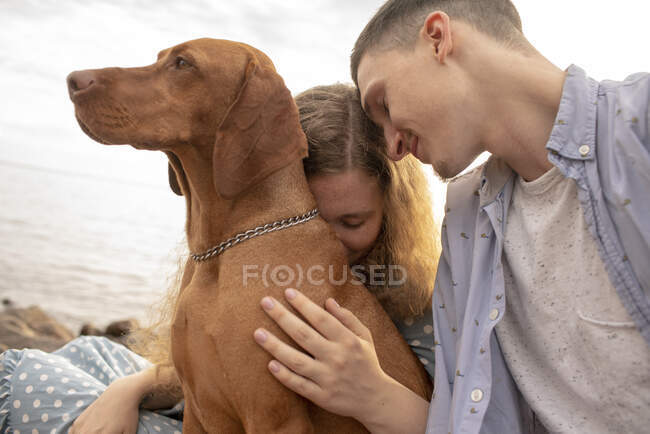 Young couple with dog at the beach — Stock Photo