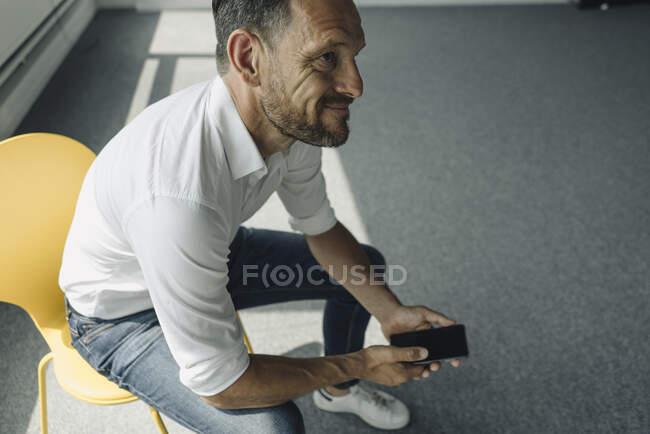 Зрелый бизнесмен сидит на стуле, держа мобильный телефон в пустом офисе — стоковое фото