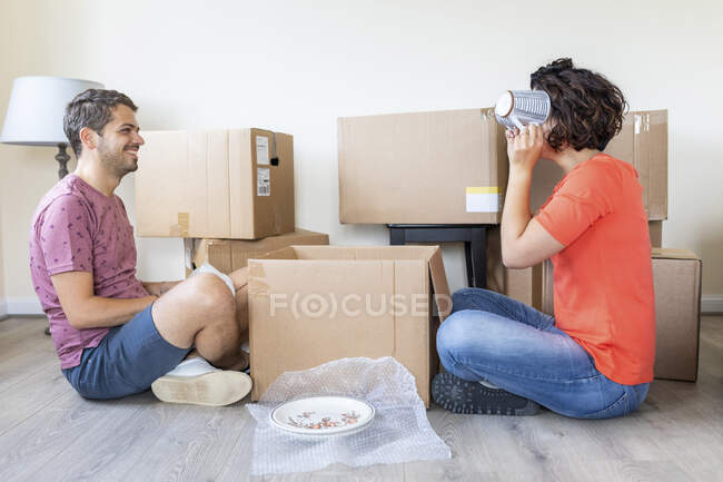 Happy couple moving into new home unpacking cardboard box — Stock Photo
