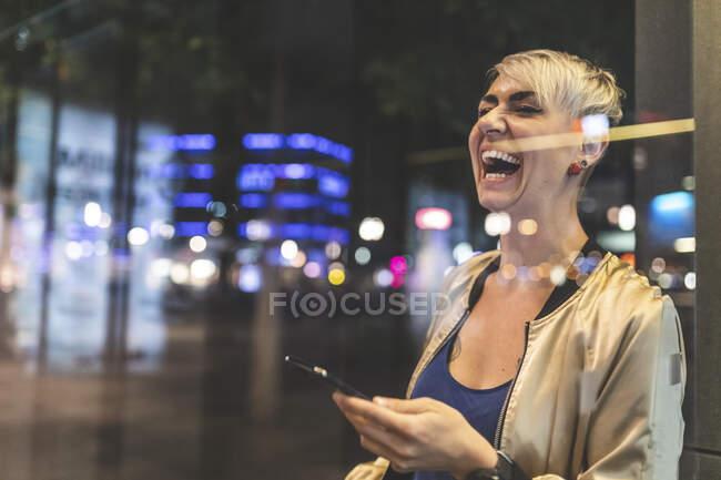 Retrato de la mujer rubia riendo usando el teléfono móvil por la noche, Berlín, Alemania - foto de stock