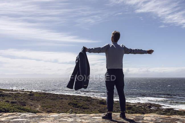 Вид сзади бизнесмена, стоящего перед морем, Кейп-Пойнт, Западный Кейп, Южная Африка — стоковое фото