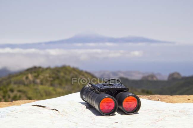 Espagne, Îles Canaries, La Gomera, Jumelles et carte située au sommet de Garajonay avec le volcan Teide en arrière-plan lointain — Photo de stock