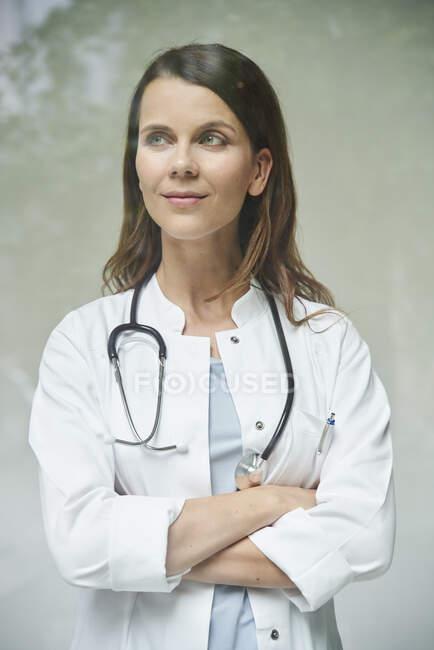 Retrato de doctora confiada detrás del cristal de la ventana - foto de stock