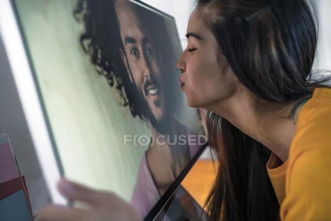 Молода жінка цілує чоловіка на екрані комп'ютера. — стокове фото