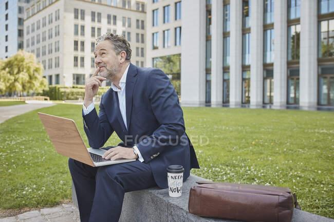 Homme d'affaires mature assis sur un mur dans la ville en utilisant un ordinateur portable — Photo de stock