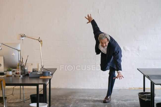 Старший бізнесмен займається гімнастикою в офісі. — стокове фото