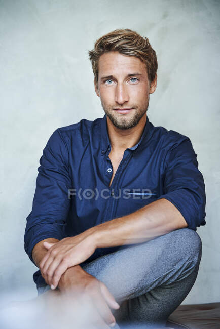 Portrait of confident young man sitting down — Stock Photo