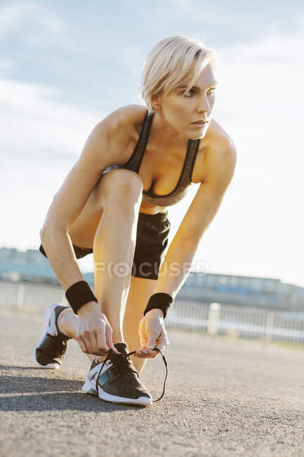 Блондинка бігає, зав'язує черевики. — стокове фото
