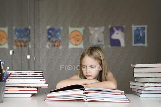 Девушка сидит за столом дома и читает книги — стоковое фото