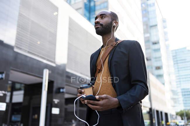 Joven empresario con café para ir escuchando música con auriculares y smartphone en la ciudad - foto de stock