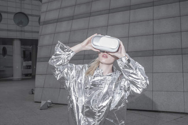 Girl in silver suit. looking through VR goggles in futuristic city — Stock Photo