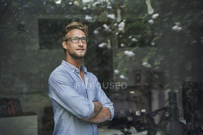 Casual giovane uomo d'affari dietro il vetro della finestra in ufficio — Foto stock