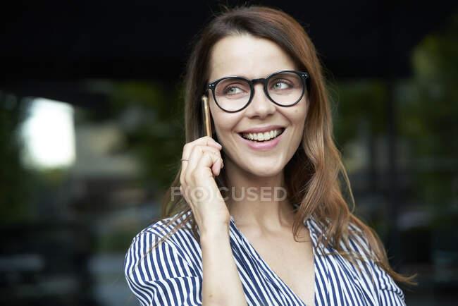 Щаслива ділова жінка розмовляє по телефону в місті. — стокове фото