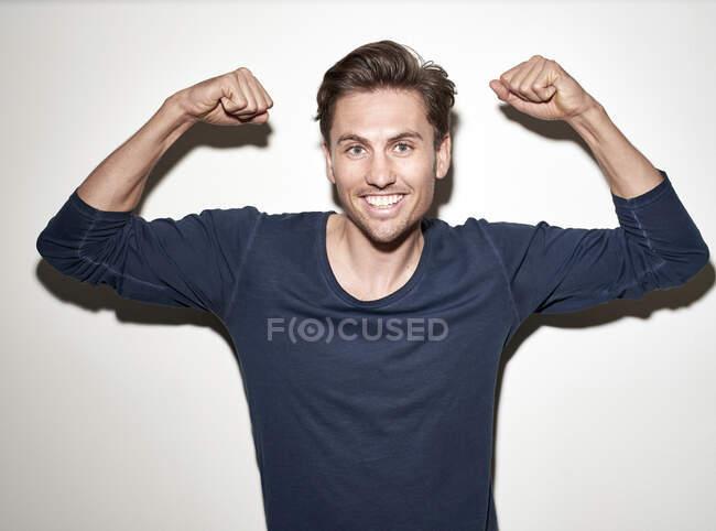 Retrato del hombre risueño flexionando los músculos - foto de stock