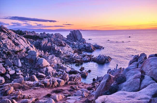 Italia, Provincia di Sassari, Santa Teresa Gallura, Riva rocciosa di Capo Testa al tramonto viola — Foto stock