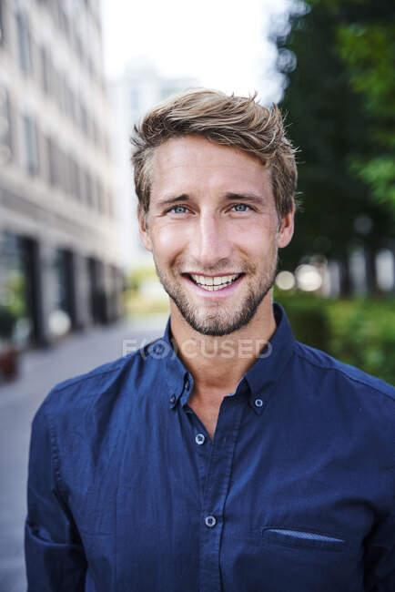 Porträt eines lächelnden jungen Geschäftsmannes in der Stadt — Stockfoto