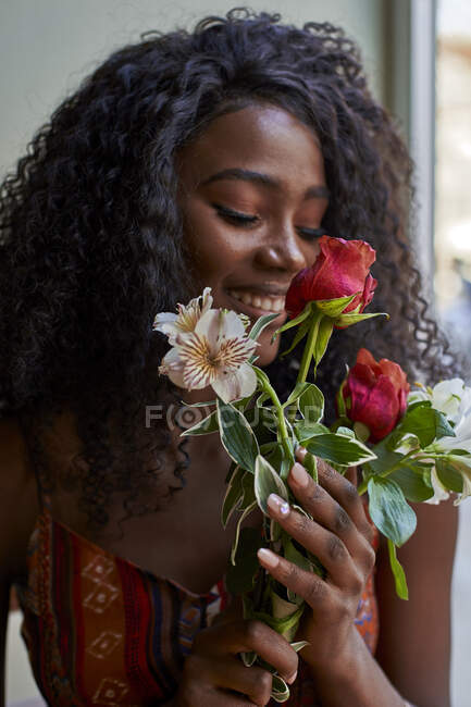 Портрет молодой африканской женщины, нюхающей цветы и улыбающейся в кафе — стоковое фото