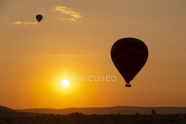 Silhouette hot air balloons flying over landscape against sky at sunset in Cappadocia, Turkey — Stock Photo