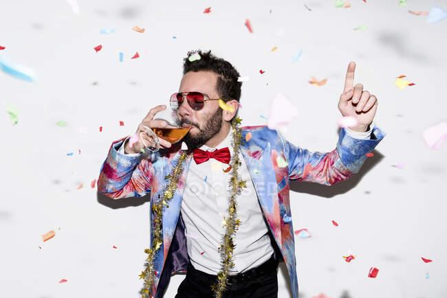 Uomo fresco ed elegante indossa un abito colorato e occhiali da sole che celebrano una festa con coriandoli e bere — Foto stock