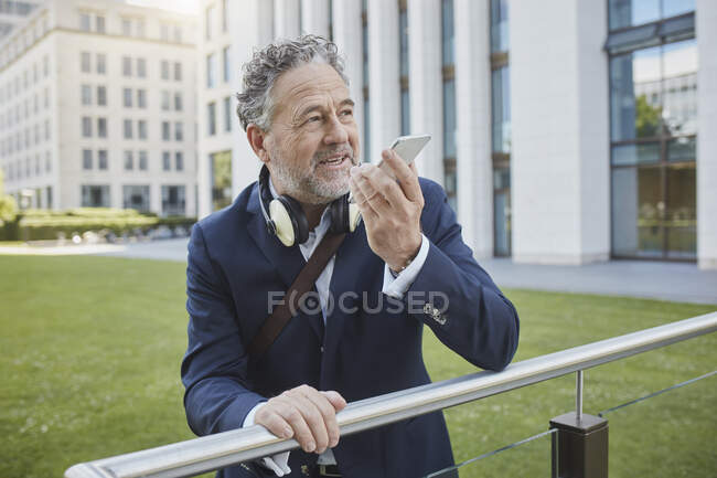 Mature businessman using smartphone in the city — Stock Photo