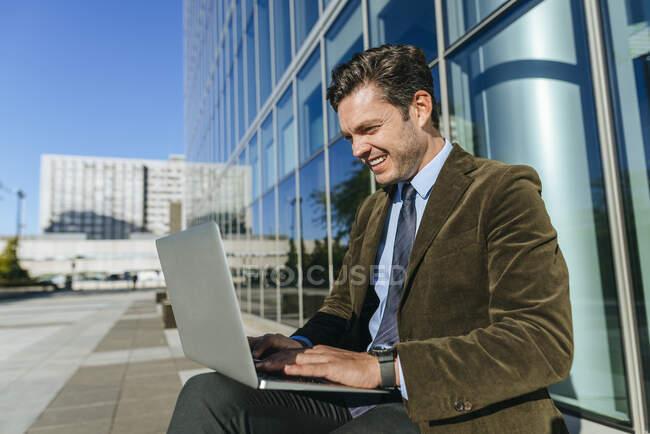 Щасливий бізнесмен, який сидить у міському діловому районі за допомогою ноутбука (Мадрид, Іспанія). — стокове фото