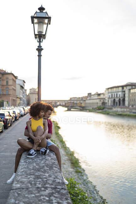 Pareja de turistas jóvenes y cariñosos sentados en una pared en el río Arno al atardecer, Florencia, Italia - foto de stock