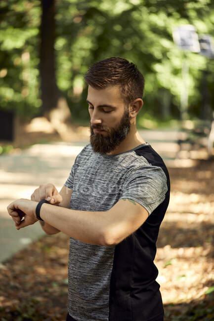 Спортивный человек в лесу проверяет свои умные часы — стоковое фото
