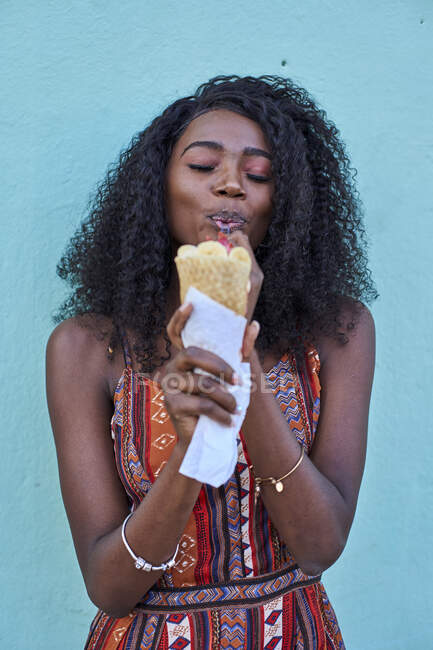 Portrait of young woman enjoying ice cream against blue wall — Stock Photo