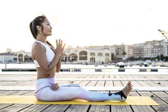 Mujer asiática practicando yoga en un muelle en el puerto - foto de stock