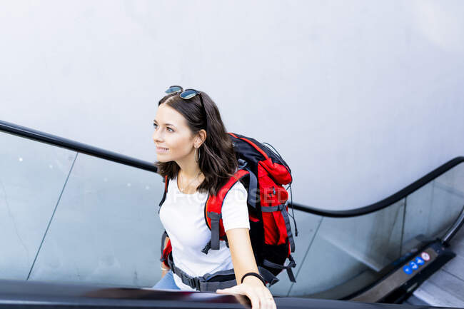Young female backpacker on escalator, Verona, Italy — Stock Photo