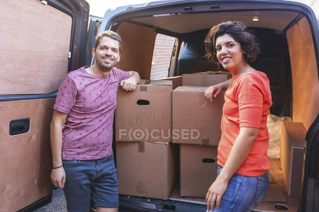 Portrait of smiling couple at van with cardboard boxes — Stock Photo