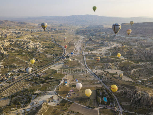 Aerial view of colorful hot air balloons flying over land at Goreme National Park, Cappadocia, Turkey — Stock Photo