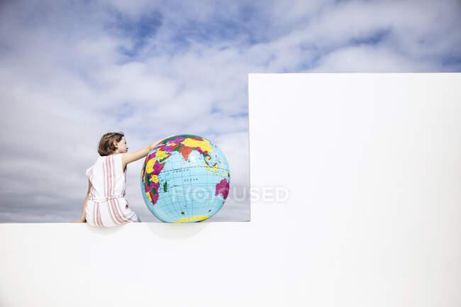 Маленька дівчинка сидить на стіні з надувною глобусом на задньому плані. — стокове фото