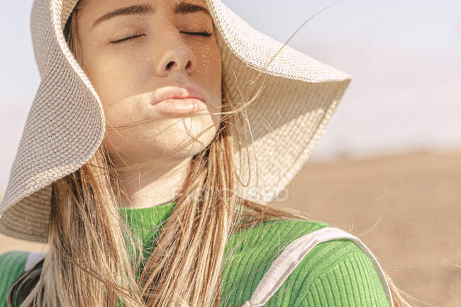 Молодая женщина в соломенной шляпе сидит в природе — стоковое фото