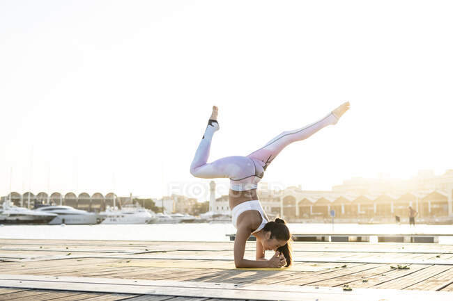 Азиатка практикует йогу на пирсе в гавани — стоковое фото