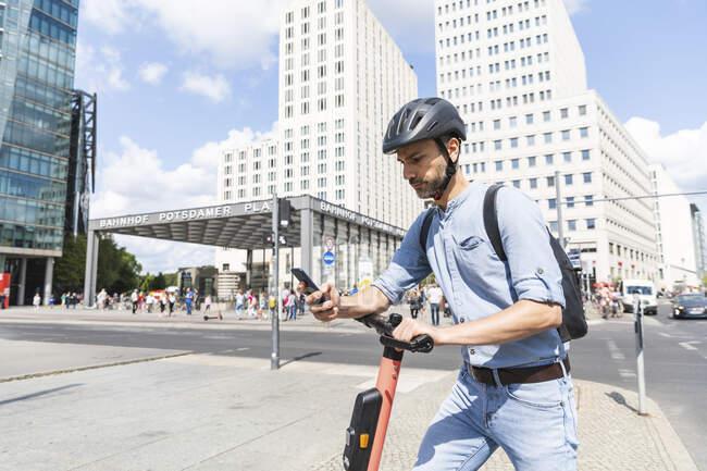 Бізнесмен дивиться на смартфон, який працює на електричному скутері в місті Берлін (Німеччина). — стокове фото