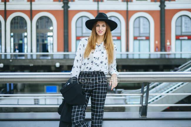 Retrato de una joven sonriente con sombrero en la estación de tren - foto de stock