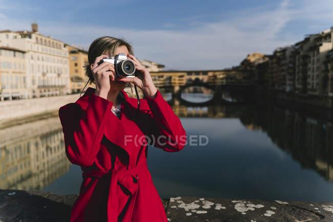 Молодая женщина фотографирует на мосту над рекой Арно, Флоренция, Италия — стоковое фото