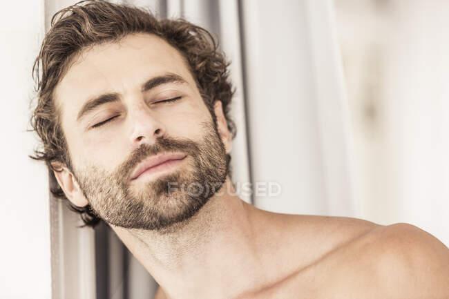 Porträt eines jungen Mannes mit Bart, geschlossenen Augen — Stockfoto