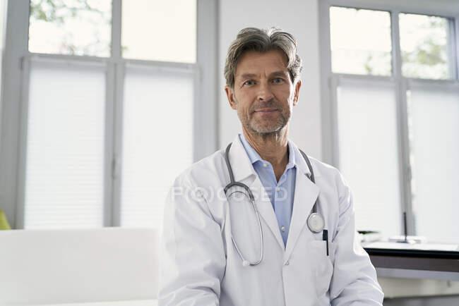 Retrato del médico confiado en su práctica médica - foto de stock