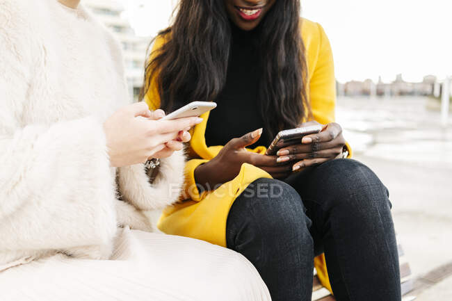 Close-up of girlfriends sitting on a bench in the city using mobile phone — Stock Photo