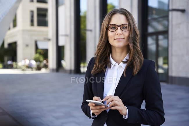 Портрет довіреної комерсантки з мобільним телефоном у місті. — стокове фото
