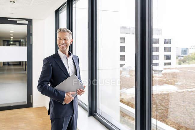 Homme d'affaires avec ordinateur portable devant la veuve de l'immeuble de bureaux — Photo de stock