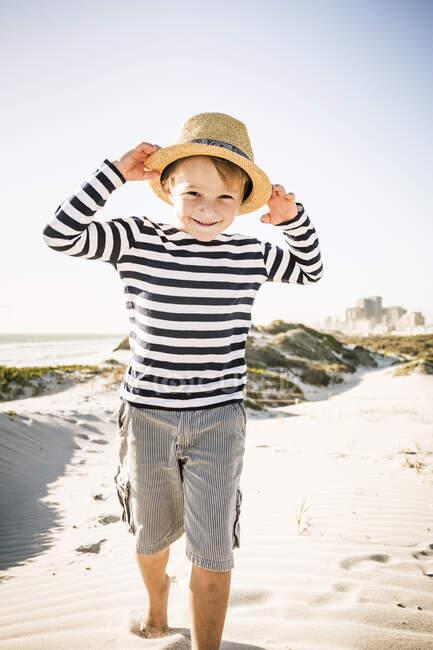 Ritratto di ragazzo sorridente con cappello sulla spiaggia — Foto stock