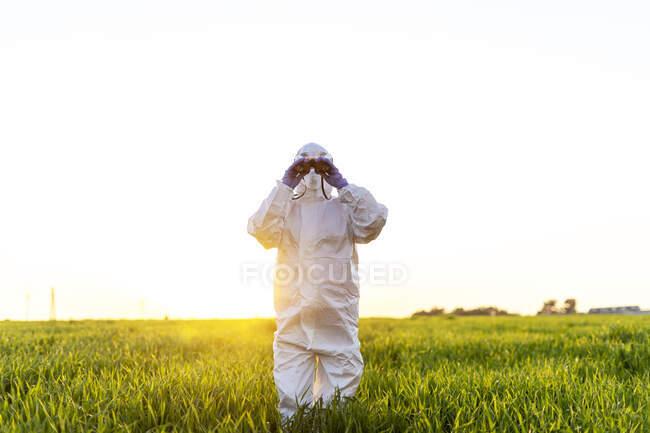 Científica investigando en el campo y mirando a través de binoculares al atardecer - foto de stock
